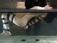 Leggy brunette gets very wet when she is bound gagged and suspended