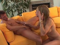 Guy fucking with cute blond shemale on yellow sofa