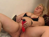 Plump mama slams a dildo all the way down her slit