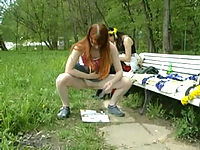 Two schoolgirls pissing near a bench in the park