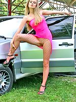 Hot blonde Alice in red fishnet pantyhose posing near the car