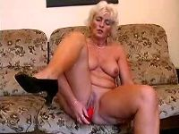 Mature sets dildo into her pussy